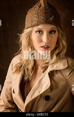 Young blonde model in a winter hat and coat in studio, Virginia Beach, VA - Stock Photo