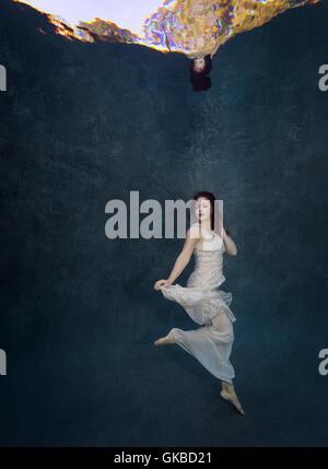Young redhead in a white dress underwater, Virginia Beach, VA - Stock Photo
