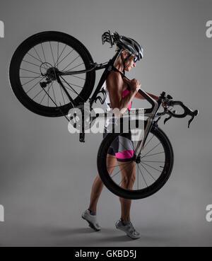 Woman in studio with her mountain bike - Stock Photo