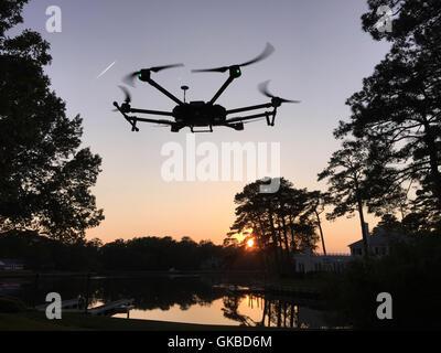 DJI Matrice 600 flying over a lake at dusk in Virginia Beach, VA - Stock Photo