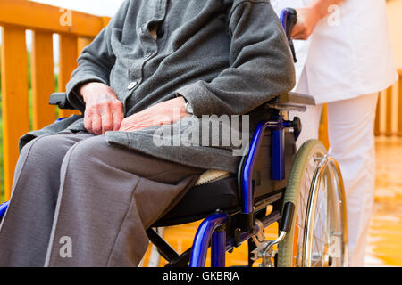 age and care - nurse and a senior in wheelchair - Stock Photo