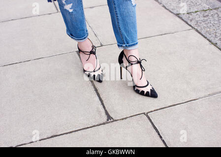 Low section of woman wearing jeans and stiletto heeled shoes - Stock Photo