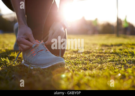 Close Up Of Woman Lacing Trainers Before Outdoor Exercise - Stock Photo