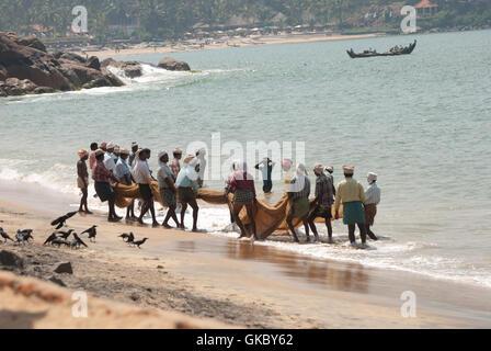 Fishermenn pulling net in at Kovalam beach from the Leela, Kovalam, India. - Stock Photo