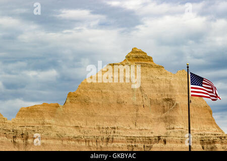 The American flag flies outside of the visitors center at Badlands National Park - Stock Photo
