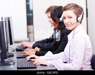 call center staff friendly with headphones on computer - Stock Photo