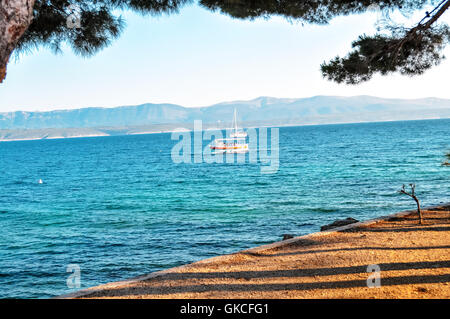 Lonely sail boat in Mediterranean sea bay, view from land - Stock Photo