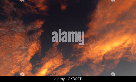 A desert sky with pink gold colored stratocumulus clouds at dusk sunset above Anza-Borrego state park - Stock Photo