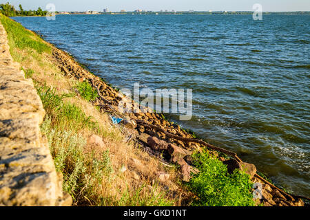 Rip-rap, or shot rock for erosion control lines the banks of Hefner lake in Oklahoma City, Oklahoma, USA. - Stock Photo