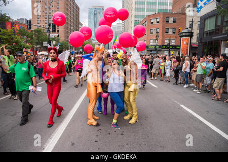 Montreal, CA - 14 August 2016: Young woman taking a selfie with dancers at Montreal Gay Pride Parade - Stock Photo