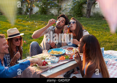 Friends Blowing Bubbles During Picnic In Garden - Stock Photo