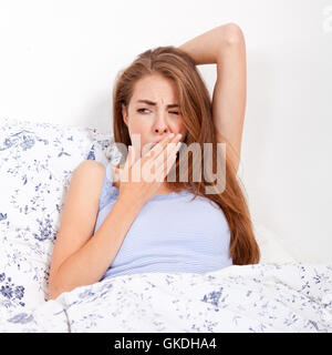 young attractive woman lies in bed and yawning in the morning - Stock Photo