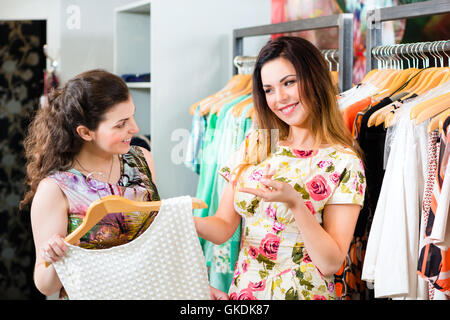 young women shopping in store or boutique - Stock Photo