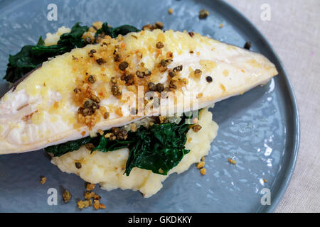 Halibut steak on potato mash with cavolo nero cabbage and capers and breadcrumbs butter - Stock Photo