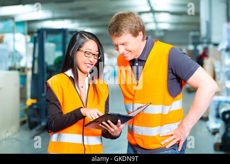 forklift driver and colleague,in storage of freight forwarding - Stock Photo
