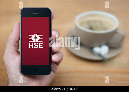 A man looks at his iPhone which displays the HSE logo, while sat with a cup of coffee (Editorial use only). - Stock Photo