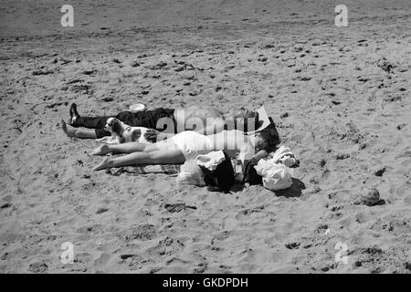 A man and woman and and their dog lying on the beach at Ayr, 1990 - Stock Photo