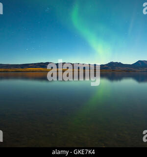 Northern lights and fall colors at calm lake - Stock Photo