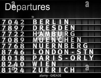 Airport departures information board - Stock Photo