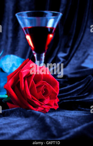 Gentle red rose and liquor in a glass - Stock Photo