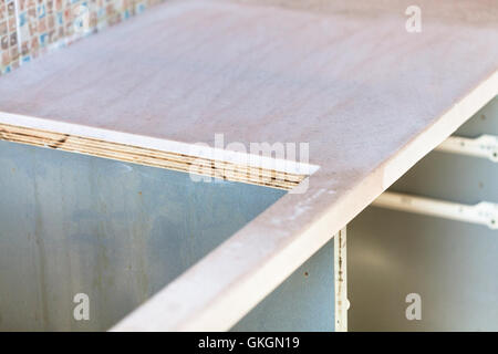 installing new tabletop on kitchen - cutout for cooking stove in new kitchen worktop from artificial stone - Stock Photo