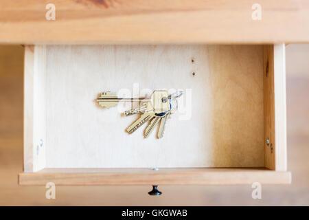 above view of bunch of door keys in open drawer of nightstand - Stock Photo