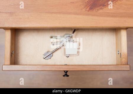 top view of bunch of door keys with keychain in open drawer of nightstand - Stock Photo