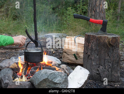 girl prepares in a cauldron on the fire, near the ax in  log - Stock Photo