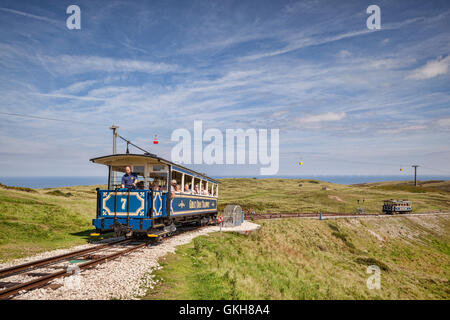 A passenger car of the Great Orme Tramway climbs from the upper passing loop as the descending car continues down, - Stock Photo