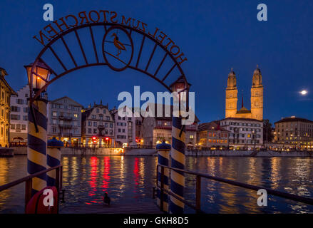 Limmatquai and Grossmunster in Zurich at Night, Switzerland - Stock Photo