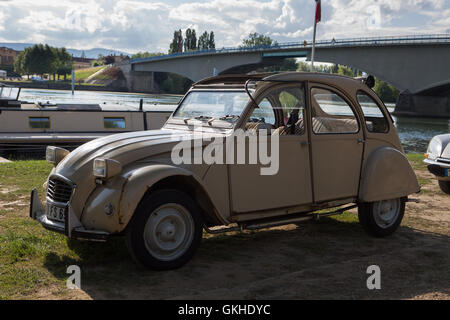 Vintage French car Citroen 2CV sitting alongside river Saone in France - Stock Photo