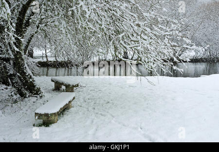 Lonely bench in a snow-covered, park - Stock Photo