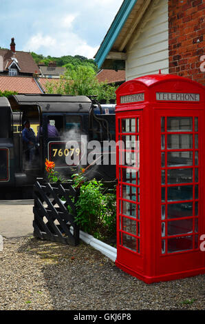 Red telephone box and steam train at Grosmont Station North Yorkshire Moors England UK - Stock Photo