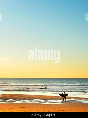 Couple surfers on the ocean beach at sunset - Stock Photo