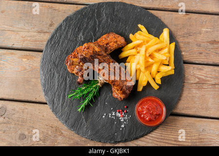 baked pork ribs with french fries and red sauce - Stock Photo