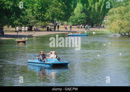 London park summer, tourists in Regent's Park enjoy a summer afternoon on the boating lake, London, UK. - Stock Photo