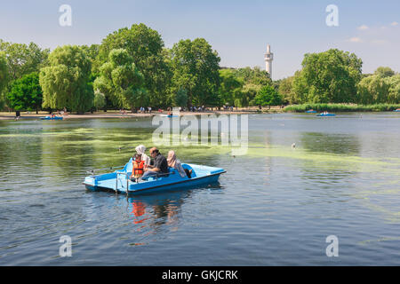 Regent's Park Lake, tourists enjoy a summer afternoon on the boating lake in Regent's Park, London, UK. - Stock Photo