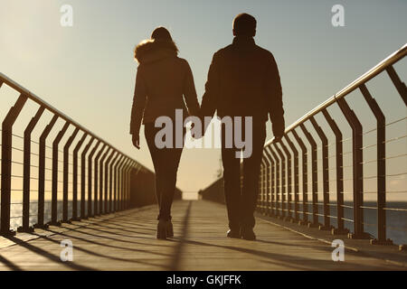 Back silhouette of a couple walking holding hands - Stock Photo