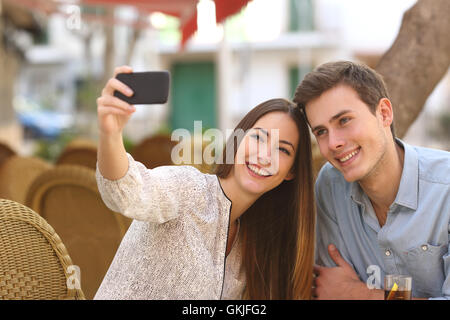 Couple taking a selfie photo in a restaurant - Stock Photo
