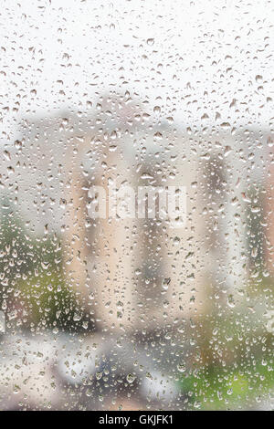 rainy weather in city - view of raindrops on window of apartment house - Stock Photo