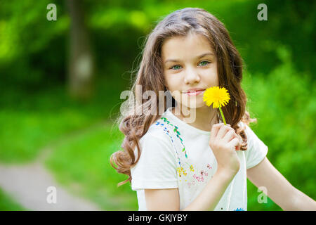 Little girl smelling a yellow dandelion in spring park - Stock Photo