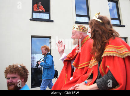 A man watches from an upstairs window as the newly crowned 'King and Queen of the Redheads' Alan O'Neill and Emma - Stock Photo
