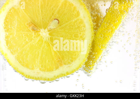 Sliced lemon in refreshing fizzy water - Stock Photo