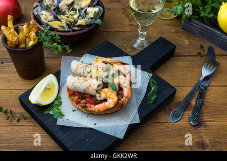 Italian food. Bruschetta with squid and prawns, tomatoes and parsley - Stock Photo