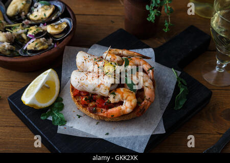 Tapas with shrimp and squid on wooden board, from top. - Stock Photo