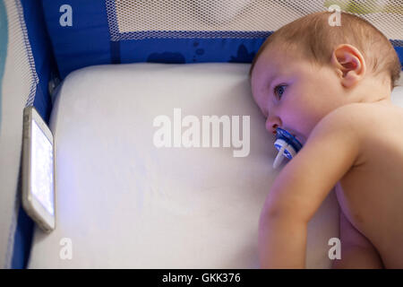 12 month old baby watching a lullaby cartoons with mobile phone on the crib - Stock Photo