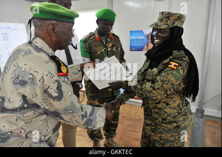 The AMISOM Deputy Chief of Staff , Col. Dahir Abrar , hands a certificate to one of the CIMIC Focal Point Officers - Stock Photo