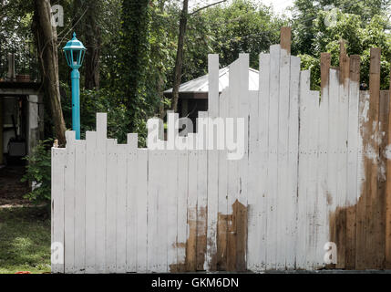 Uneven boards in a fence are partially whitewashed, with a lamp post  and garden in back - Stock Photo