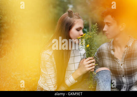 Loving couple teens together. Girlfriend and boyfriend together. The boy looks at the girl. Girl smelling a bouquet - Stock Photo