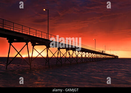 Red hellish sunset over sea horizon behind historic timber jetty of Ceduna town on Great Australian Bight. STormy - Stock Photo